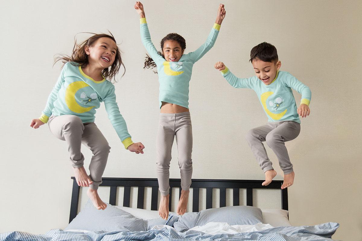 パジャマを着た子供たちがベッドの上で跳ねてる